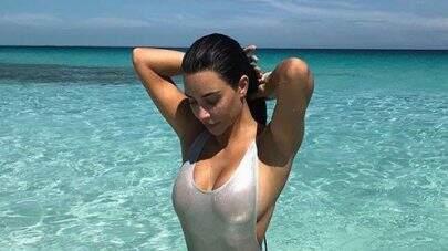 Kim Kardashian exibe corpão ao posar na praia com maiô ousado