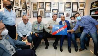 Bolsonaro posa com uma placa escrita 'CPF Cancelado' e parlamentares dizem que ele 'ri das quase 400 mil vidas perdidas'