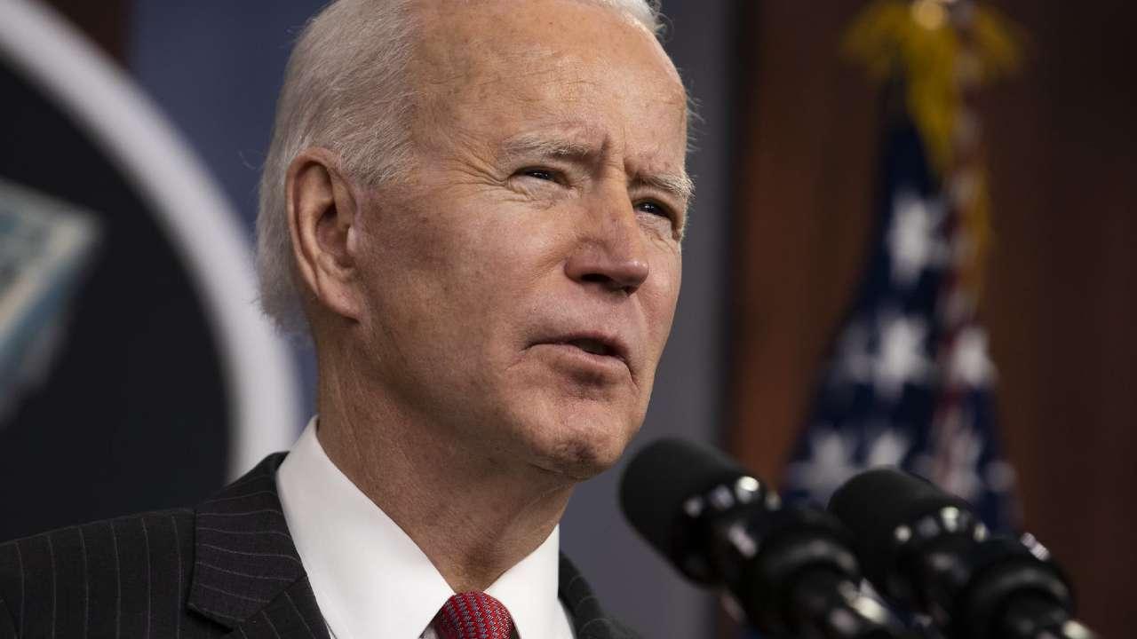 Presidente Biden falando em frente a um microfone