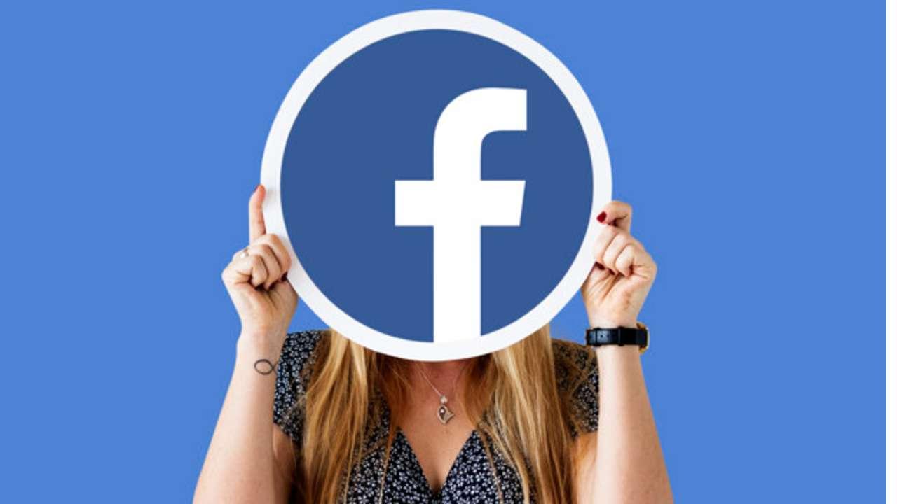 Mulher segurando placa do Facebook na frente do rosto