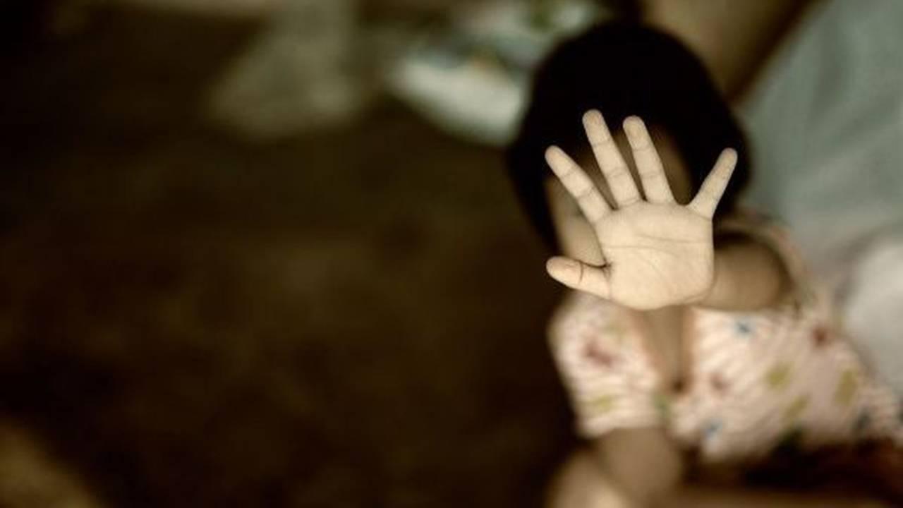 Criança com mão aberta a frente do seu rosto