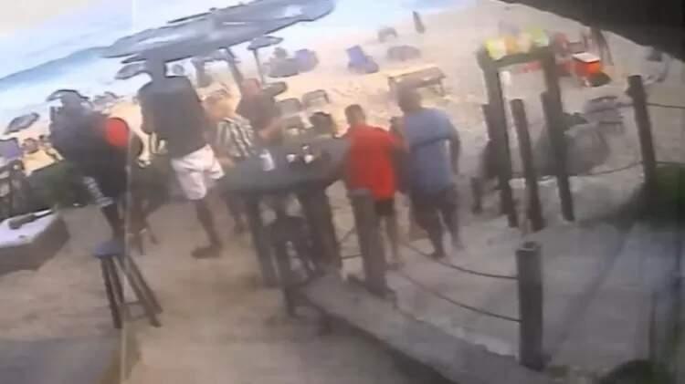 Foto mostra MC Kevin, de camiseta vermelha, se apoiando para andar