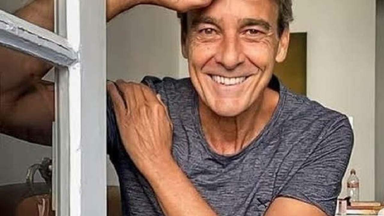 Foto mostra Alexandre Borges apoiado com os braços na porta e sorrindo