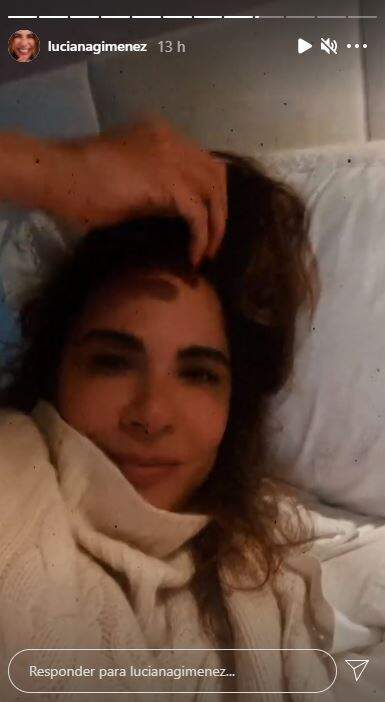 Luciana Gimenez, de tricot creme e cabelos soltos deitada na cama